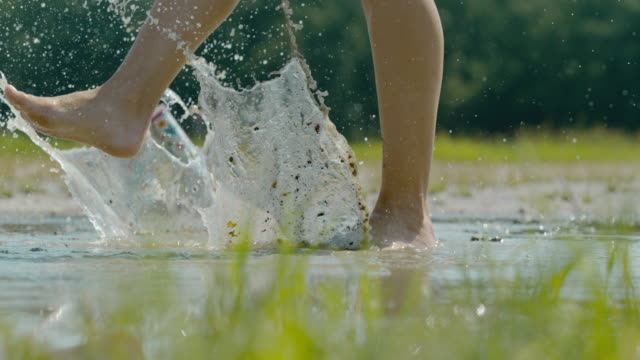 SLO MO Barefoot woman splashing in the muddy puddle. Happy woman. Super slow motion medium shot of a barefoot woman making a big splashes in the muddy puddle. focus on foreground stock videos & royalty-free footage