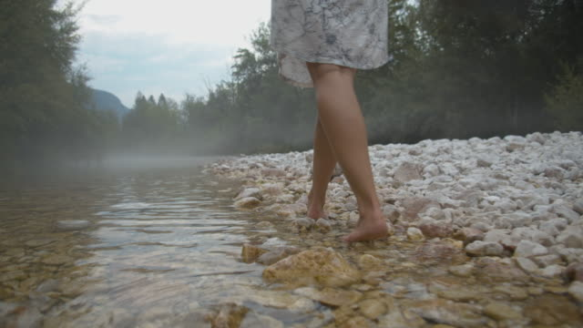 SLO MO Barefoot woman walking in the stream