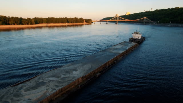 Barge sails along the river near the city port on sunset aerial footage video
