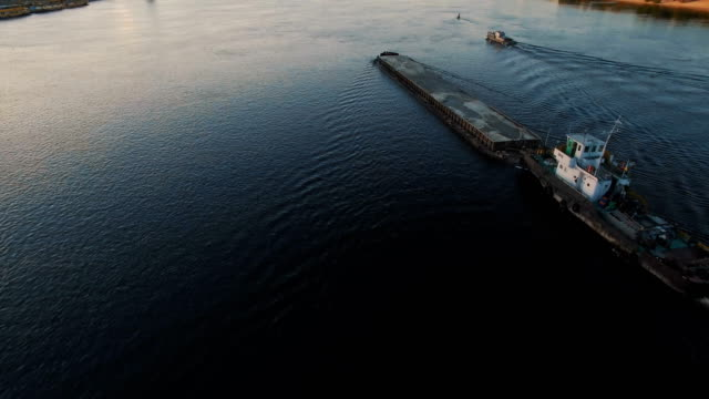 barge sails along the river near the city port on sunset aerial footage - chiatta video stock e b–roll