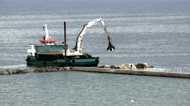barge with crane positions reefs to protect the beach - chiatta video stock e b–roll