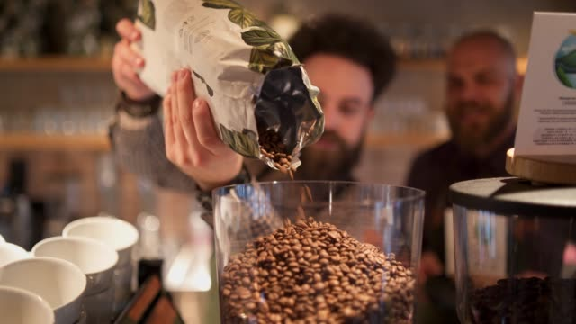 barista adding coffee beans to coffee grinder - barista stock videos and b-roll footage