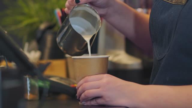 barista fügt milch aus krug gießen in papierglas nahaufnahme - milchkrug stock-videos und b-roll-filmmaterial