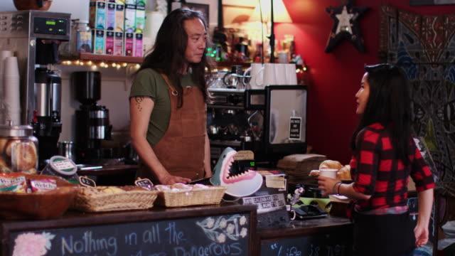 vidéos et rushes de barista bavarder avec le client dans cafe - relation client