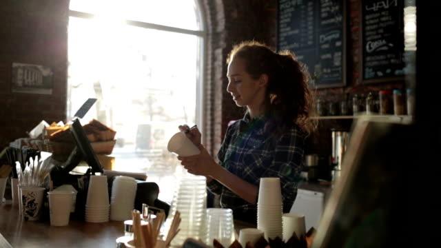 バリスタ コーヒー ・ ハウスは、カップに名前を書いて、笑みを浮かべて ビデオ