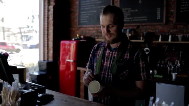barista coffee house schrieb den namen auf den becher und lächelnd - barista stock-videos und b-roll-filmmaterial