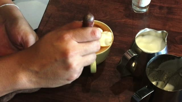 barista create latte art on wood table