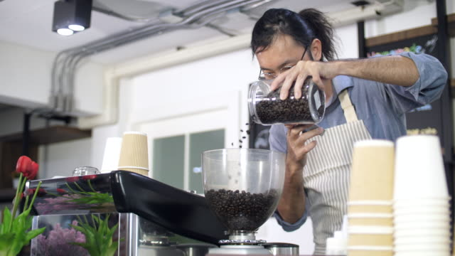 Barista Filling Coffee Beans into Coffee Grinder