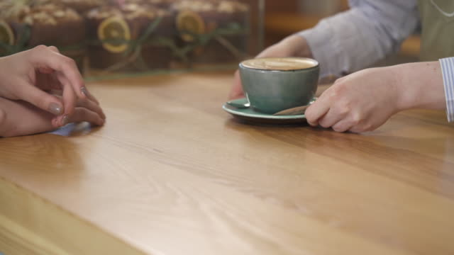Barista giving a cup of hot aromatic cappuccino to a client. Morning coffee. Favorite beverage. Close-up video, isolated, on blurred background Barista giving a cup of hot aromatic cappuccino to a client. Morning coffee. Favorite beverage. Close-up video, isolated, on blurred background positioning stock videos & royalty-free footage