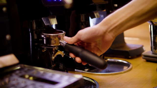 barista grinding coffee beans with coffee machine and and making a shot of espresso coffee - grindare video stock e b–roll