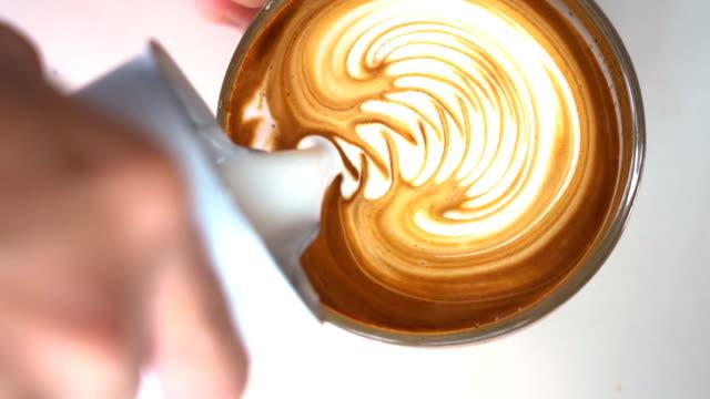 SLO MO Barista hand making latte art coffee.