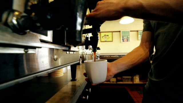 Barista in local coffee shop preparing fresh hot beverage for customer video