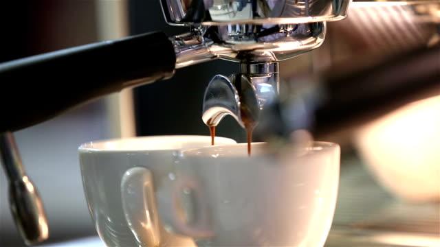 Barista makes coffee in the coffee machine. White coffee mugs. Close up.