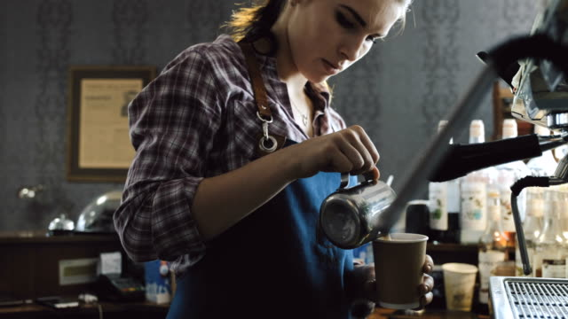 Barista making a drink Handheld close up video of female barista pouring steamed milk into a coffee cup wait staff stock videos & royalty-free footage