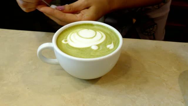 barista machen, gesicht und herz form latte kunst auf heiße matcha grüner tee im café café tragen - milchkaffee stock-videos und b-roll-filmmaterial
