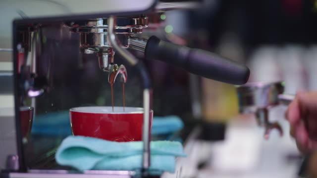 vídeos y material grabado en eventos de stock de barista haciendo café con cafetera en la cafetería. la máquina barista se pone taza a la máquina para esperar café líquido en la cafetería. cuando el inicio del trabajo o el entrenamiento es tiempo de relax para beber taza caliente. - café negro
