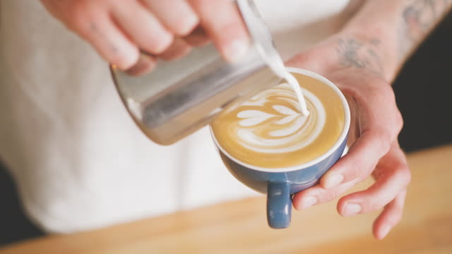 vídeos de stock e filmes b-roll de barista making latte art at a cafe - fazer