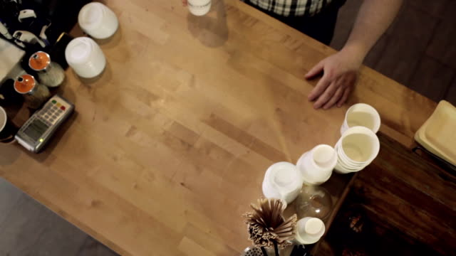 Barista passes coffee to visitor. View from the top video