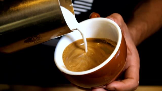 barista pouring milchschaum zum coffe cup auf latte. herstellung von latte art. - milchkaffee stock-videos und b-roll-filmmaterial