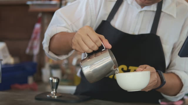 Barista pouring steamed milk into coffee cup making latte art Rosetta pattern.