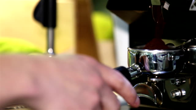 Barista pours coffee in the portafilter espresso machine. Close up. video