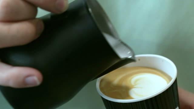 barista pours milk into coffee. - espresso filmów i materiałów b-roll