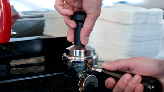 Barista presses ground coffee using tamper video