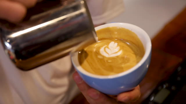 A barista serving a latte with a floral pattern in the milk froth