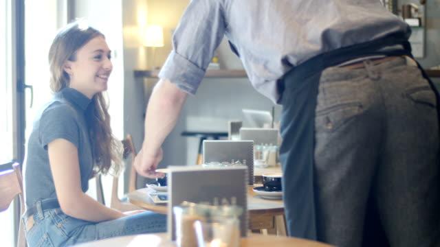 バリスタコーヒーをお出しする、男性と女性の友人 ビデオ