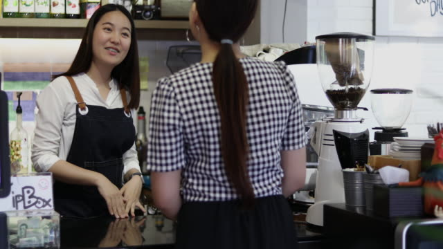 Barista serving customer and Woman is paying for coffee by credit card in coffee shop video