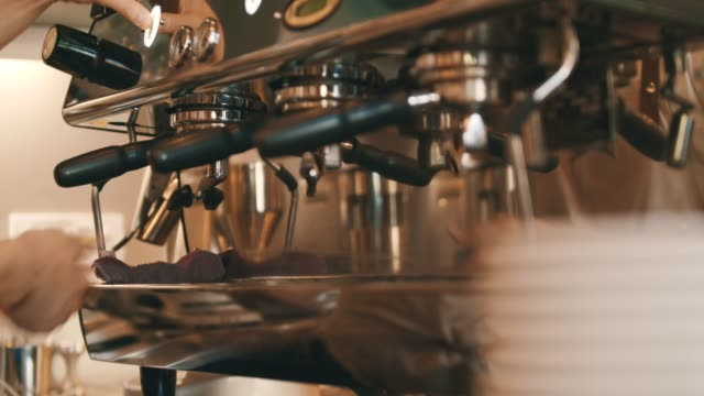 Barista steaming coffee in cap