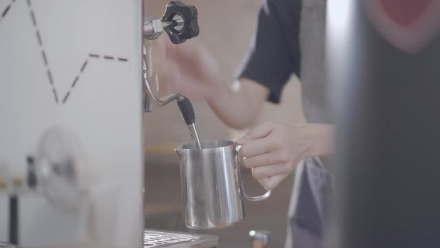 barista steaming milk at espresso machine in cafe - pentola a vapore video stock e b–roll