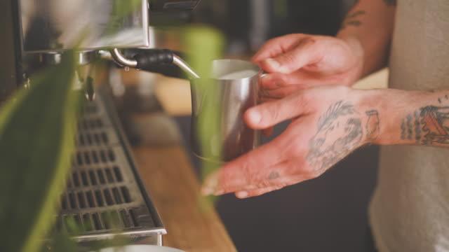 barista dampfende milch von der espressomaschine - milchkrug stock-videos und b-roll-filmmaterial