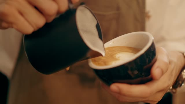Barista working as the coffee shop while making latte art hot coffee menu video