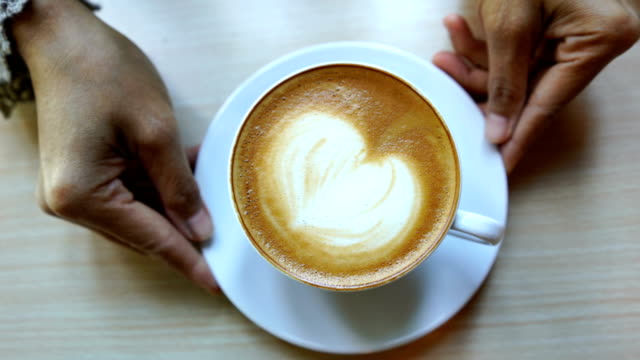 barista's hand showing latte art coffee ready for drink - pausa caffè video stock e b–roll