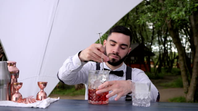 barkeeper on bar counter stirring alcohol with ice in glass, barman makes alcoholic drink outdoors, Summer cafe video