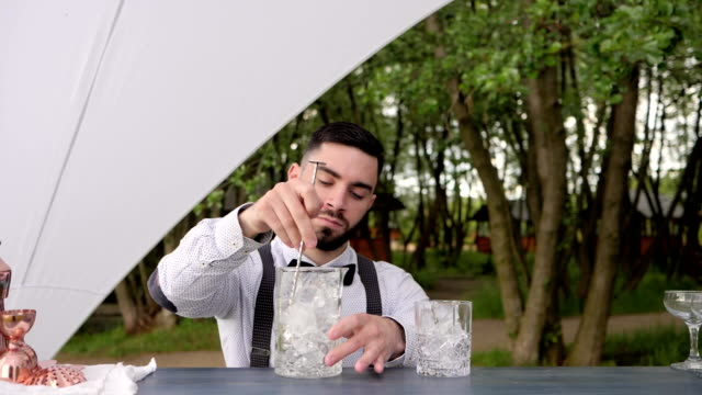 barkeeper stirring ice cubes bar spoon on nature, glass with ice on bar counter, bartender makes cooling beverage to fresh air, event Service video