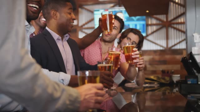 Barmaid Serving Group Of Male Friends On Night Out For Bachelor Party Making Toast Together