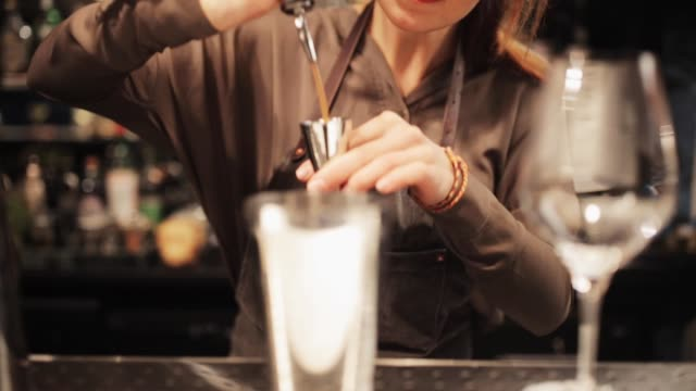 barmaid with glass and stirrer preparing cocktail - bartender stock videos and b-roll footage