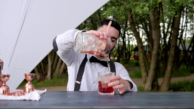barman adds alcohol in juice with ice on bar counter, bartender prepares cooling cocktail with ice, event Service video