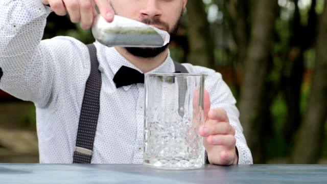 barman at work put ice into glass close-up, barkeeper at bar counter put ice cubes in glass for alcohol video