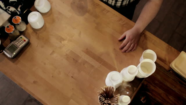 Barman gives up coffee to buyer. View from the top video