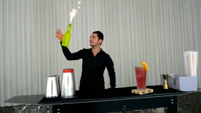 Barman juggling and making flair bartending moves at a bar with bottles and fireworks video