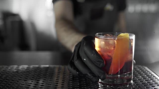 vídeos de stock, filmes e b-roll de braga fez um coquetel negrone e colocá-lo no bar. - provando usando a boca