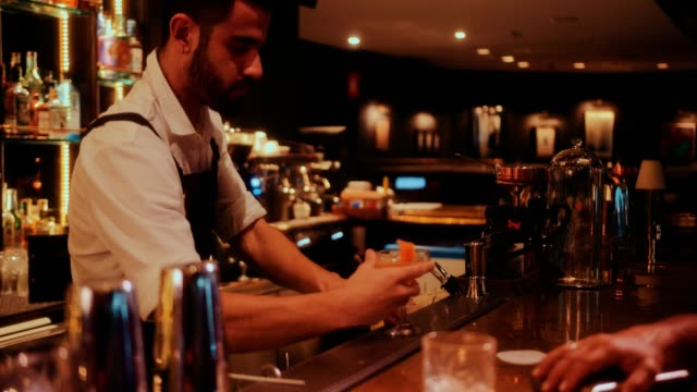 Barman making and serving cocktail on luxurious retro bar counter Young handsome bartender preparing and serving cocktail on luxurious retro restaurant bar counter bar counter stock videos & royalty-free footage