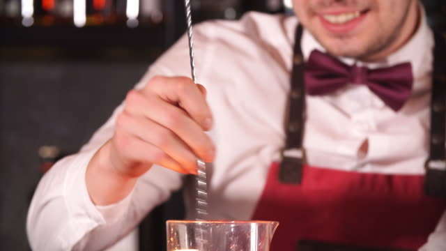 Barman mixing cocktail ingredients with a long spoon in high glass Barman mixing cocktail ingredients with a long spoon in high glass filled with ice cubes on the bar counter spoon stock videos & royalty-free footage