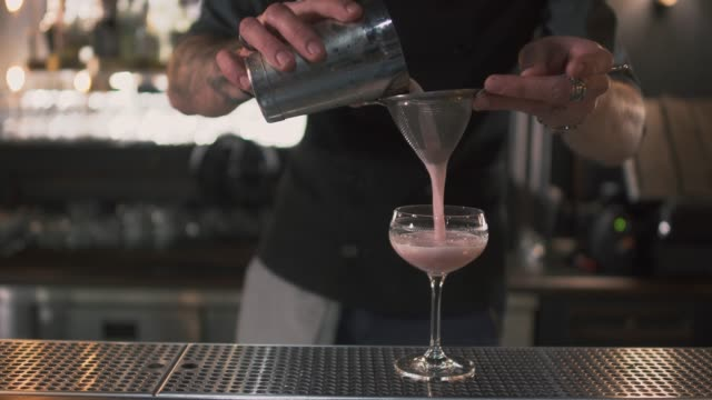 Barman pouring pink milk cocktail through a sieve in high glass on bar counter video