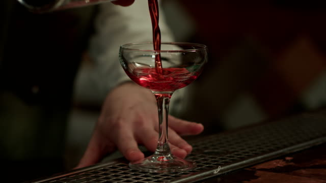 Barman pouring red alcohol preparing cosmopolitan into champagne glass video