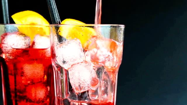 Barkeeper Gießen rote Aperitif cocktail mit zwei Orangenscheiben und Eiswürfel auf schwarzem Hintergrund – Video