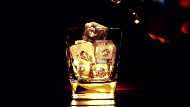 barman pouring whiskey in the glass with ice cubes on wood table and black dark background, focus on ice cubes, whisky relax time on warm atmosphere - brandy video stock e b–roll